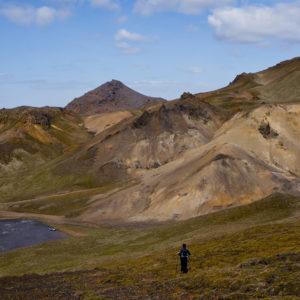 Gríðarlegt sár mitt í gróinni hlíð. Bílinn á borstæðinu sýnir stærðarhlutföllin.